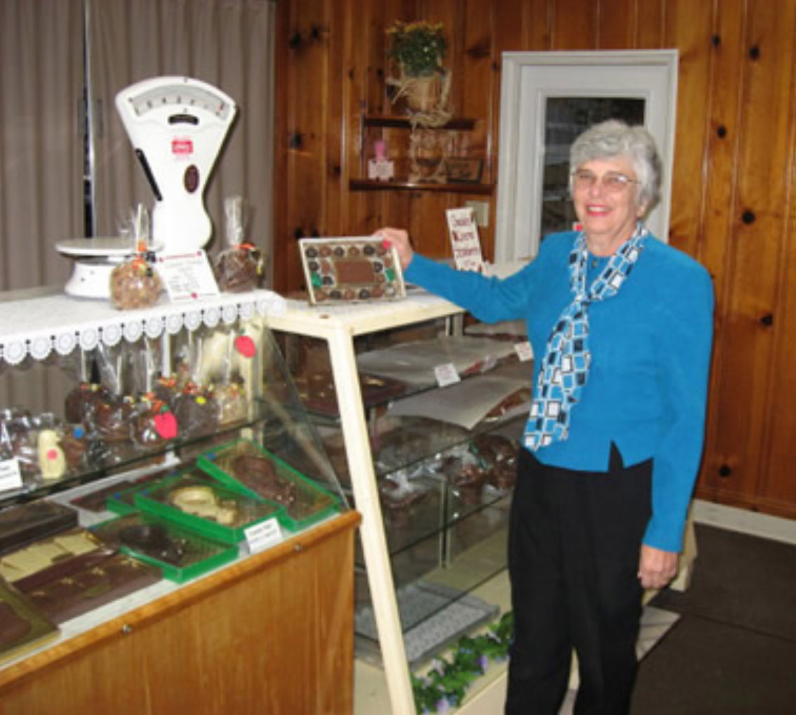 Barbara in front of display cases filled with chocolate at store.