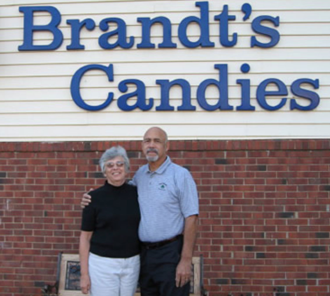 Owners of Brandt's Candies standing outside store.