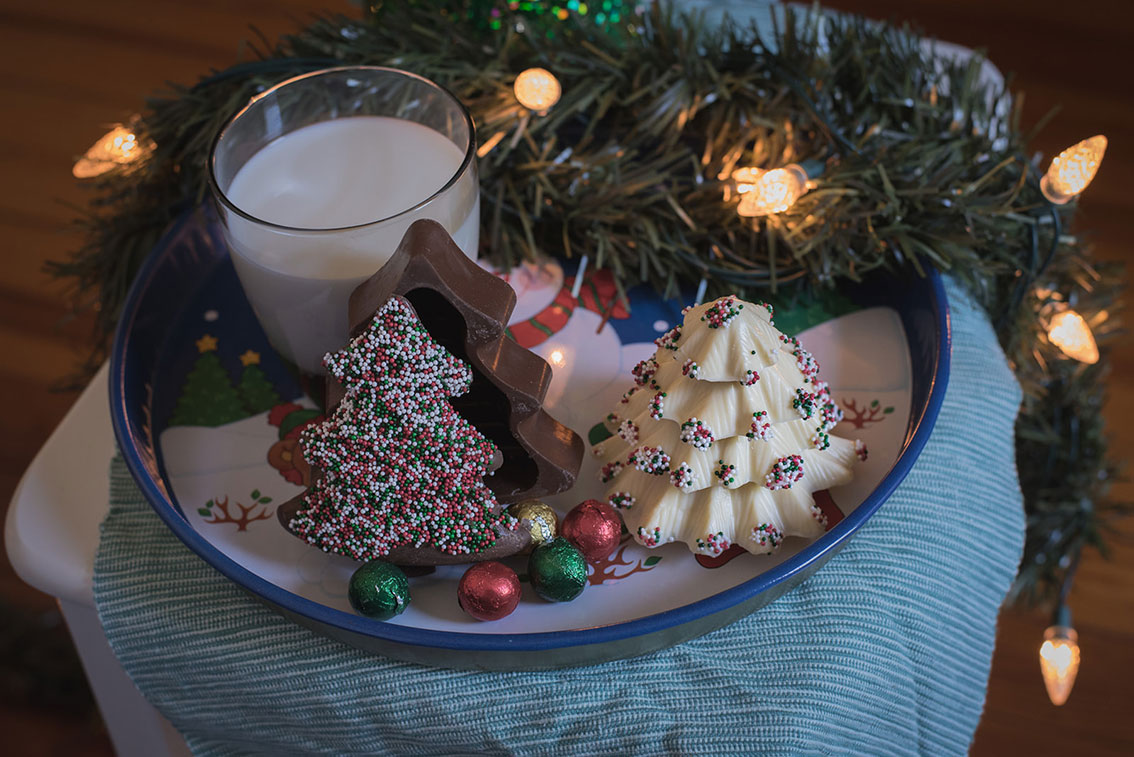 Tray filled with chocolate Christmas trees and a glass of milk.